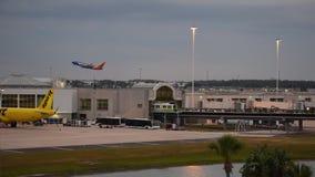 Самолет Southwest Airlines принимая на предпосылку захода солнца на международном аэропорте Орландо