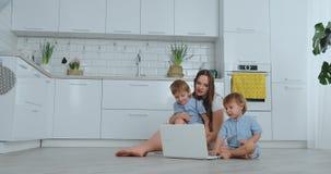 самомоднейшая технология Мама современной квартиры любя и 2 небольших сынов сидя на поле во взгляде живущей комнаты на сток-видео