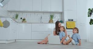 самомоднейшая технология Мама современной квартиры любя и 2 небольших сынов сидя на поле во взгляде живущей комнаты на акции видеоматериалы