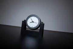 Самомоднейшие черные часы на черной таблице в офисе Стоковая Фотография