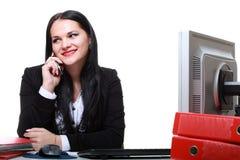 Самомоднейший телефон женщины дела говоря сидя на столе офиса стоковое изображение