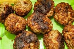 Самонаведите сделанные шарики мяса говядины на зеленой плите стоковые фотографии rf
