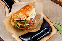 Самонаведите сделанный гамбургер с говядиной, луком, томатом, салатом и сыром Свежий крупный план бургера на деревянной деревенск Стоковые Фотографии RF