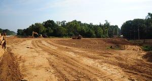 Самосвалы и бульдозеры освобождают землю для новой проезжей части Стоковое фото RF