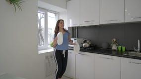 Самостоятельно дома, смешная домохозяйка околпачивая вокруг и поет с блюдами в руках на кухне в выходных сток-видео