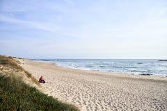 Самостоятельно женщины усаженные на пляж стоковые изображения rf
