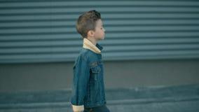 Самостоятельно мальчик идет вниз по улице и мысль Сторона маленького серьезного грустного мальчика быть сток-видео