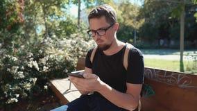 Самостоятельно мужской турист осматривает на экране его смартфона, сидит в районе парка сток-видео