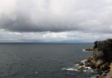 Самостоятельно путешественник на скалах бурного моря в западной Ирландии стоковое изображение rf