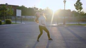 Самостоятельно тонкая девушка танцора танцует в дворе домов в городе во времени захода солнца, завихряя и выполняя шаг балета сток-видео