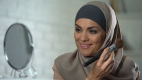 Самоуверенная арабская дама делая макияж, прикладывая порошок щеткой, женственность акции видеоматериалы