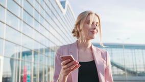 Самоуверенная горячая молодая белокурая девушка в элегантной розовой куртке идет крупным аэропортом и использует ее мобильный тел акции видеоматериалы