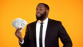 Самоуверенные удовлетворенные афро-американские наличные деньги доллара показа бизнесмена, доход стоковые фотографии rf