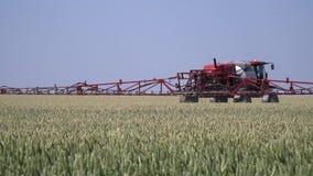 Самоходный спрейер с длинными оружиями управляет через пшеничное поле акции видеоматериалы