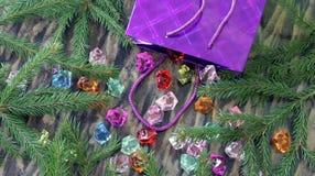 Самоцветы разливают из пакета подарка на рождественской елке Стоковая Фотография RF