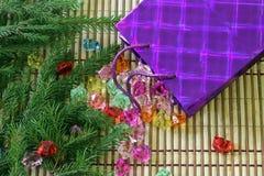 Самоцветы разливают из пакета подарка на рождественской елке Стоковая Фотография