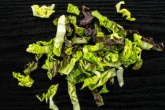 Самоцвет свежего сырцового зеленого салата красный маленький на черной древесине Стоковое фото RF