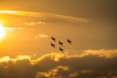 Самолеты летая на заход солнца Стоковые Изображения