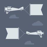 Самолет-бипланы летания с пустым знаменем приветствиям Стоковое фото RF