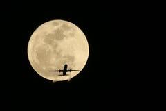 Самолет двигателя проходя перед полной луной реальным не цифров Стоковая Фотография
