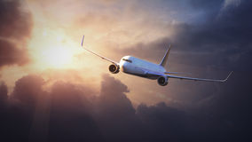 Самолет в небе на заходе солнца стоковая фотография