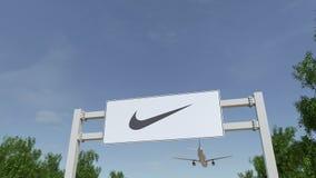 Самолет летая над афишей рекламы с надписью и логотипом Найк Редакционное 3D представляя зажим 4K видеоматериал