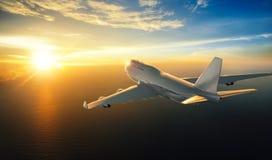 Самолет летая над морем во время захода солнца Стоковое фото RF
