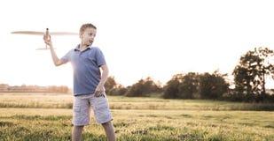 Самолет мальчика бросая на солнечной предпосылке стоковое фото rf