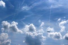 Самолет среди облаков в расстоянии Стоковое Фото