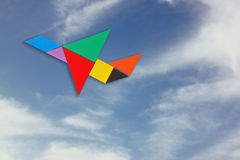 Самолет сделанный от головоломки tangram 1 предпосылка заволакивает пасмурное небо Стоковые Изображения