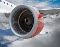 Самолет с красным летанием двигателя в облаках Стоковая Фотография RF