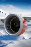 Самолет с красным летанием двигателя через облака Стоковая Фотография