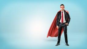 Само-конечно бизнесмен в красной накидке и маске стоя с рукой в его карманн на голубой предпосылке Стоковое Изображение RF