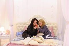 Самые лучшие женские друзья наблюдают новости на интернете на smartphone и cha Стоковая Фотография RF