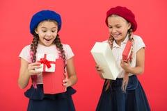 Самые лучшие подарки для детей Маленькие девочки детей в коробках подарков владением школьной формы и беретов Дети возбужденные о стоковое изображение