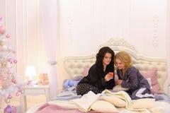 Самые лучшие женские друзья наблюдают новости на интернете на smartphone и cha Стоковое фото RF