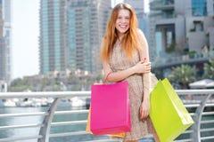 Самые лучшие покупки лета Маленькая девочка держа хозяйственные сумки пока вымачивайте Стоковая Фотография RF