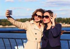 Самые лучшие подруги принимают selfie используя их телефон на яркий и солнечный день Стоковое Изображение