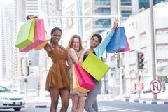 Самый лучший день для shopaholics 3 друз держа хозяйственные сумки Стоковые Изображения