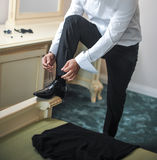 Самый лучший человек получая готовый на специальный день Groom кладя на ботинки по мере того как он получает одетым в официально  Стоковое Изображение RF