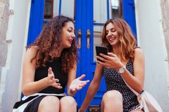 2 самых лучших женских друз беседуя пока использующ smartphone в городе Счастливые девушки говоря и смеясь над Стоковые Фото