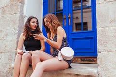 2 самых лучших женских друз беседуя пока использующ smartphone в городе Счастливые девушки подростка говоря и смеясь над Стоковое фото RF