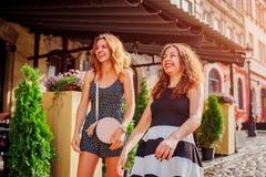 2 самых лучших женских друз встречали кафем в городе Девушки смеясь над и имея потехой outdoors Стоковые Фото