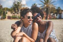 2 самых лучших женских друз сидя совместно на усмехаться пляжа Стоковые Изображения RF