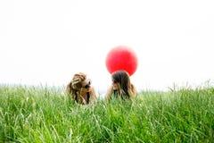 2 самых лучших подруги кладя на траву Стоковое фото RF