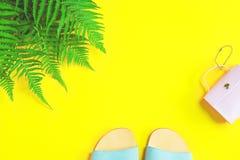 Сандалии и портмоне лета на желтой предпосылке стоковая фотография