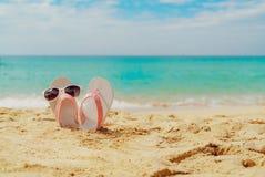 Сандалии пинка и белых, солнечные очки на пляже песка на взморье Случайный шлоп-шлоп и стекла стиля моды каникула территории лета стоковое изображение