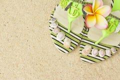 Сандалии, seashells, и frangipani на песке Стоковые Изображения