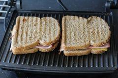 Сандвичи ветчины и сыра выпечки в кухне стоковое изображение rf