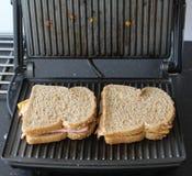 Сандвичи ветчины и сыра выпечки в кухне стоковые изображения rf